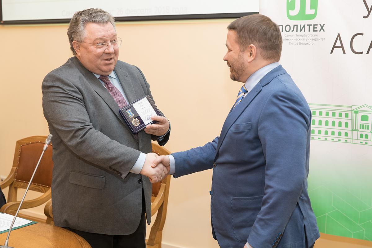 Заместитель постпреда Республики Саха (Якутия) при Президенте РФ Ю.Н. Кравцов вручает ректору юбилейную медаль